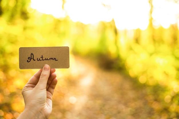 Herfsttekst op een kaart. meisje met kaart in herfst park in zonnige stralen.