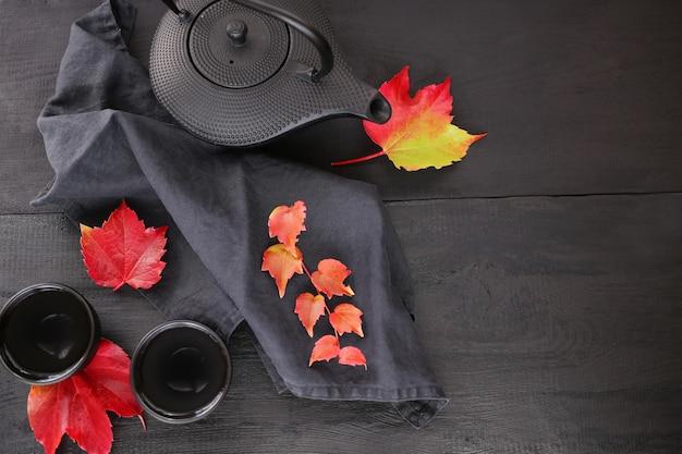 Herfstthee in minimalistische stijl. zwarte theepot in aziatische stijl en heldere herfstbladeren