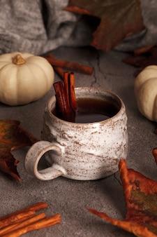Herfstthee met kaneel. thee in de herfstscène. herfstbladeren en pompoenen