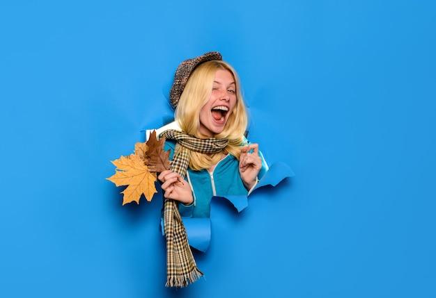 Herfstuitverkoop knipogend meisje in pet met bladeren korting seizoenverkoop gelukkige vrouw met blad op zoek