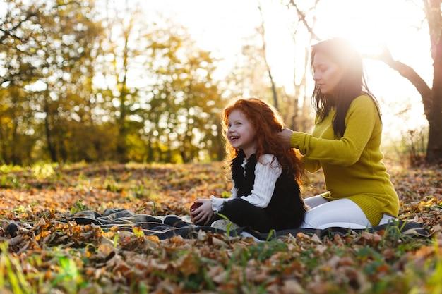 Herfstvibe, familieportret. charmante moeder en haar dochter met rood haar hebben veel plezier op de gevallenen