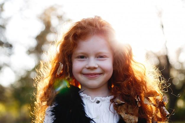 Herfstvibe, kindportret. charmant en rood haar meisje ziet er gelukkig staan op de gevallen l