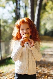 Herfstvibe, kindportret. het charmante en rode haarmeisje kijkt gelukkig etend een roomijs in a