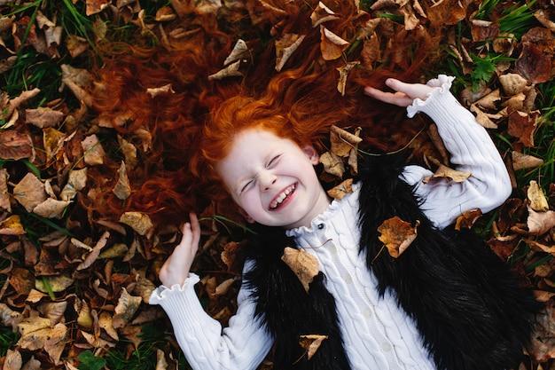 Herfstvibe, kindportret. het charmante en rode haarmeisje kijkt gelukkig liggend op gevallen gevallen