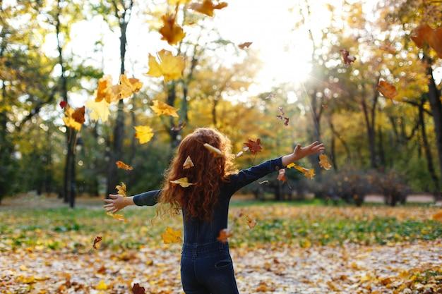 Herfstvibe, kindportret. het charmante en rode haarmeisje kijkt gelukkig lopend en spelend op t