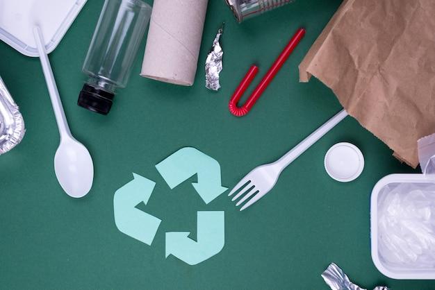 Hergebruik verminderen het recycle flat lay-concept met plastic, papier en polyethyleen afval. het beeld van de ecologiemuur met recyclingssymbool.