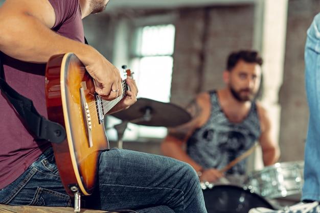 Herhaling van rockband. basgitarist, elektrische gitarist en drummer op zolder.