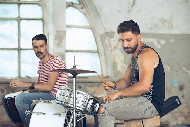 Herhaling van rockband. elektrische gitarist en drummer achter het drumstel.