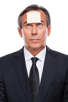 Herinnering. portret van een gefrustreerde volwassen man in formalwear en een zelfklevende notitie op zijn voorhoofd die tegen een witte achtergrond staat