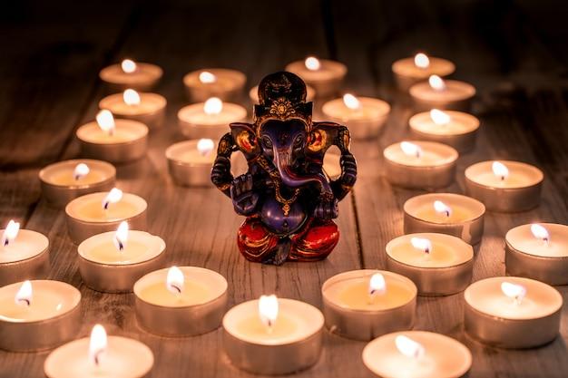 Herinneringsbeeldje van indische god ganesha onder kaarsen.