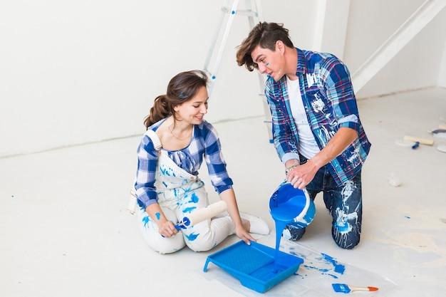 Herinrichting, renovatie en mensen concept - portret van paar giet verf