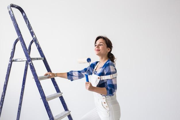 Herinrichting, renovatie, nieuw huis en mensenconcept - jonge aantrekkelijke donkerbruine vrouw die reparatie zelf doet.