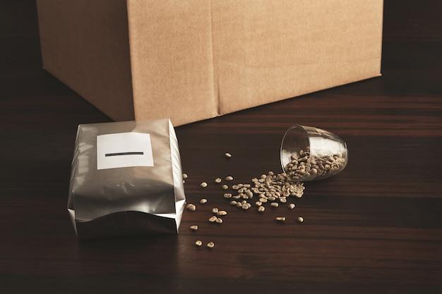 Hermetisch zilveren pakket gevuld met vers gebakken gebrande koffie om het aroma te behouden op rode houten tafel bij gevallen transparante beker met uitgespreide rauwe groene gepelde koffiebonen en kartonnen doos