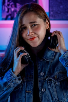 Hermosa mujer dj alegre disfrutando de escuchar musica door sus auriculares mientras mezcla musica