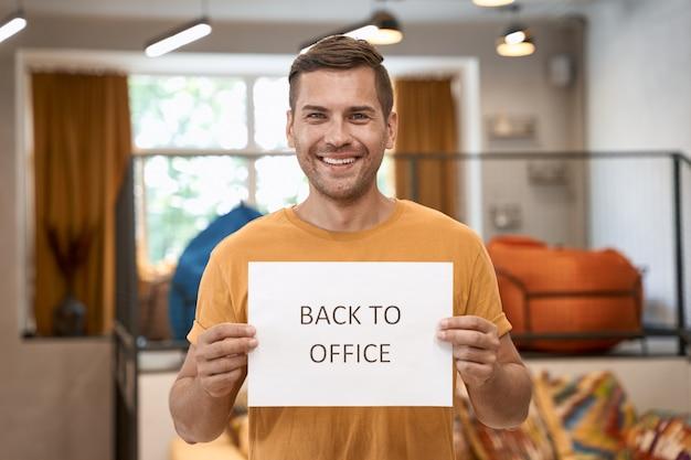 Heropening van het bedrijf na lockdown jonge gelukkige man die papier met tekst terug naar kantoor laat zien op camera