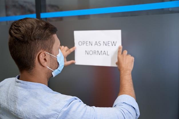 Heropening van het zakelijke achteraanzicht van een jonge man met een beschermend gezichtsmasker dat een open bord met tekst plakt