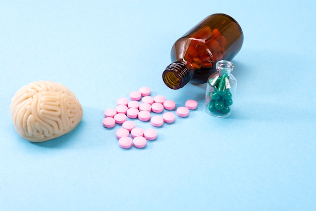 Hersenen met witte pillen in een glazen fles. sommige pillen voor de hersenen. symbolisch voor medicijnen, psychofarmaca, nootropica en andere medicijnen. geneeskunde. hersenbehandeling