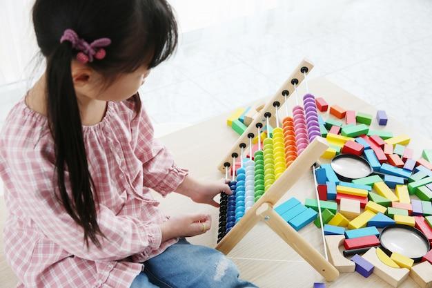Hersenontwikkeling in de vroege kinderjaren met het telraam. kleuterschoolkinderen die kleurrijk houten telraam grijpen