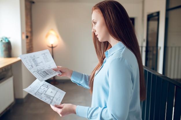 Hersenwerk. profiel van een jonge, mooie langharige vrouw in een lichte blouse die mediteert met een bouwplan in een verlichte kamer
