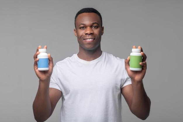 Herstel. vrolijke aantrekkelijke donkere man met verpakkingen van vitamines in handen staan ?? in de studio