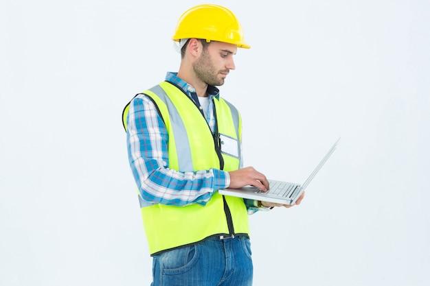 Hersteller in reflecterende werkkleding met behulp van laptop