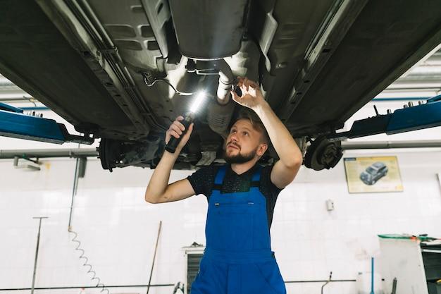 Herstellers die bodem van auto met lamp inspecteren
