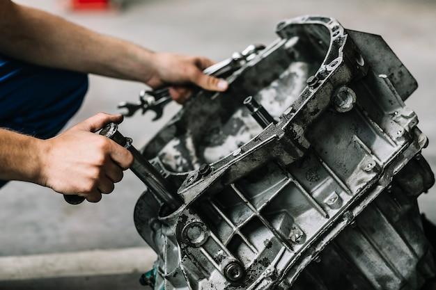 Herstellers met moersleutels die automotor bevestigen