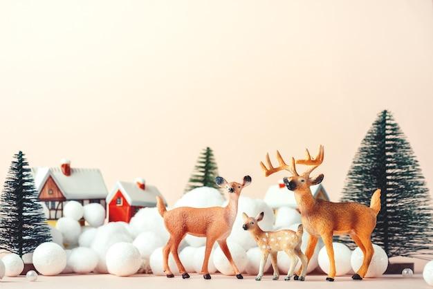 Herten familie op kerstavond op de achtergrond van landelijke huizen,