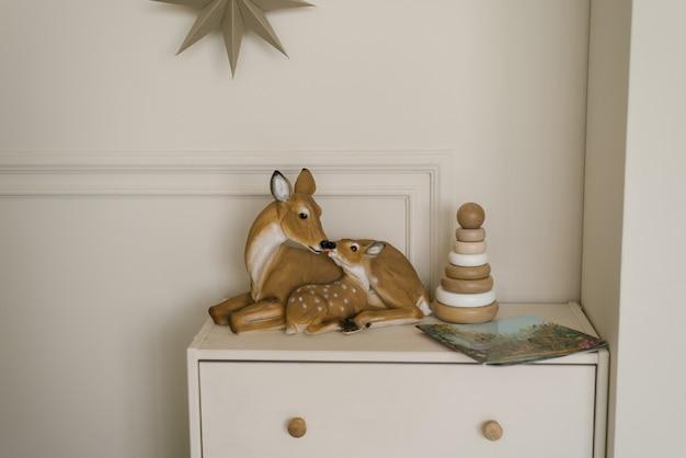 Hertenbeeldjes en een houten speelgoedpiramide voor kinderen op de ladekast in het interieur van de moderne kinderkamer
