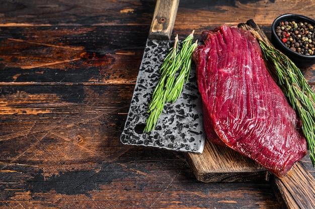 Hertenbiefstuk van rauw vlees op een snijplank met rozemarijn.