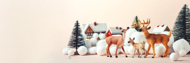Hertenfamilie op kerstavond op de achtergrond van landelijke huizen, kerstmodel Premium Foto