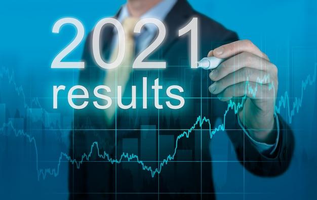 Herziening van de economische resultaten van 2021. zakenman schrijft 2021 resultaten op virtueel scherm. vorig jaar beoordeling in het bedrijfsleven. economische indicatoren, het overwinnen van de crisis en het economisch herstel na de pandemie van het coronavirus
