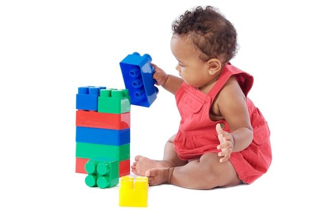 Het aanbiddelijke babymeisje spelen met bouwstenen