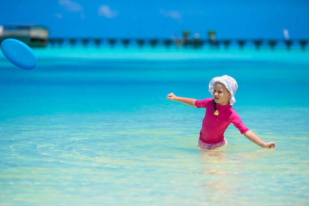 Het aanbiddelijke gelukkige meisje heeft pret bij ondiep water op strandvakantie
