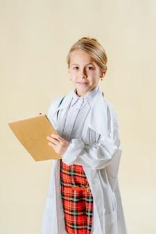 Het aanbiddelijke glimlachende meisje kleedde zich als geïsoleerde arts met stethoscoop