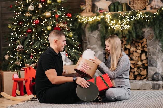 Het aanbiddelijke huwelijkspaar zit thuis dichtbij kerstboom en open haard met giftdozen