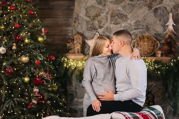 Het aanbiddelijke huwelijkspaar zit thuis dichtbij kerstboom en open haard