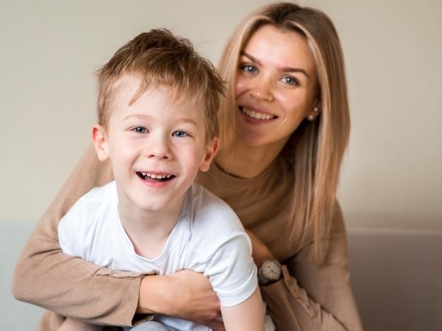 Het aanbiddelijke jonge jongen en moeder glimlachen