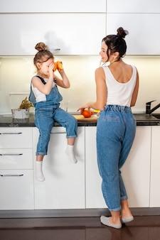 Het aanbiddelijke jonge meisje spelen met moeder in de keuken