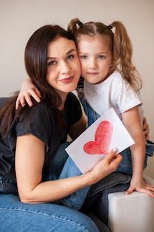 Het aanbiddelijke jonge meisje stellen met haar moeder