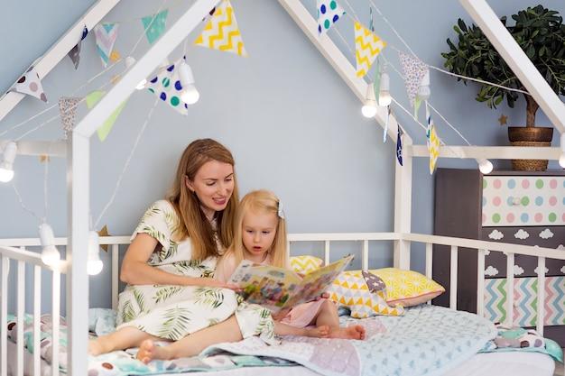 Het aanbiddelijke meisje en haar jonge moeder lezen een boek en glimlachen terwijl het zitten in verfraaid huisbed bij slaapkamer
