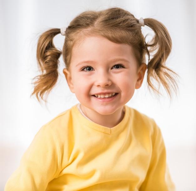 Het aanbiddelijke meisje glimlacht en kijkt
