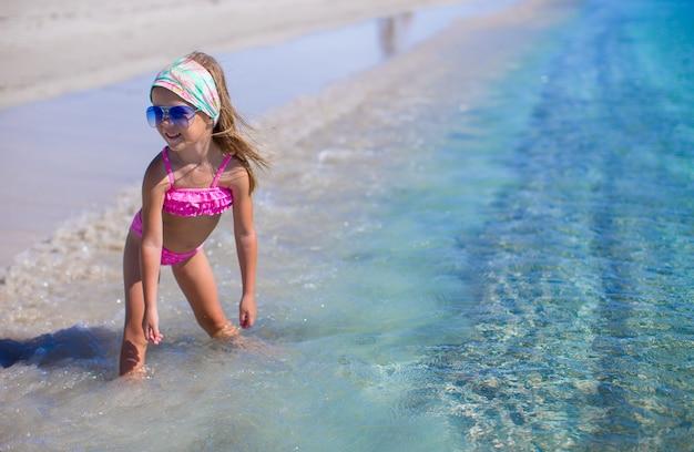 Het aanbiddelijke meisje heeft pret in ondiep water bij tropisch strand