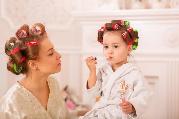 Het aanbiddelijke meisje met haar moeder in haarkrulspelden past make-up toe. moeder leert dochter cosmetica te gebruiken. schoonheid dag. meisjes zijn zulke meisjes.