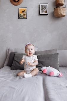 Het aanbiddelijke meisje speelt thuis met stuk speelgoed eenhoorn op bed. concept van kinderdag. gelukkige baby's, familiedag
