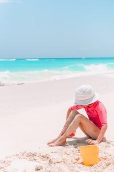 Het aanbiddelijke meisje spelen met strandspeelgoed op wit tropisch strand