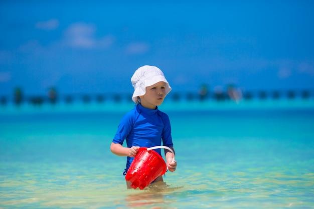 Het aanbiddelijke meisje spelen met strandspeelgoed tijdens tropische vakantie