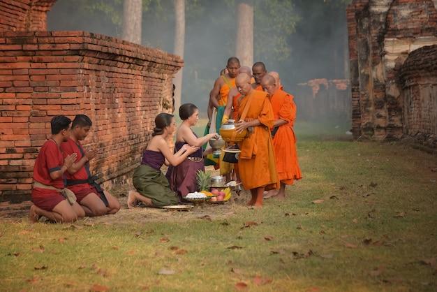Het aanbieden van aalmoezen aan monniken is de verdienste van het boeddhisme op de vastendag in een van de oude tempels in de provincie phra nakhon si ayutthaya, thailand
