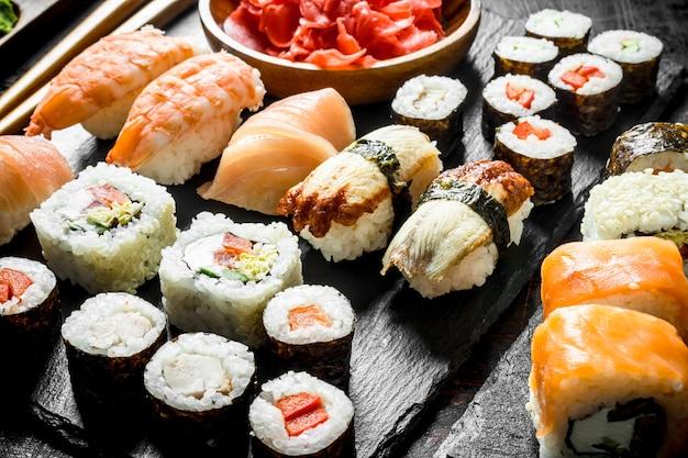 Het aanbod van verschillende soorten japanse sushi en broodjes. op donkere rustieke tafel