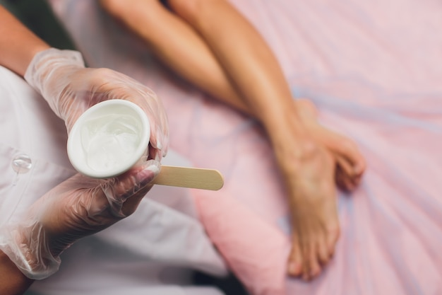 Het aanbrengen van een contactgel vóór de procedure van laser ontharing. toepassing van suikerpasta voor de procedure van shugaring.